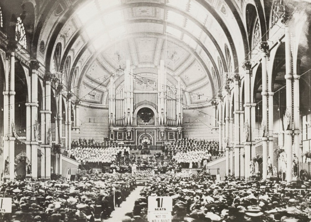 A choir stands around the Grand Willis Organ during a concert in the Great Hall at Alexandra Palace